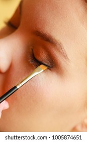 Visage concept. Close up woman getting make up on eyelids. Applying eyeshadow with brush, closed eyes.