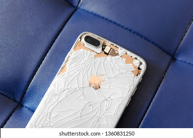 VISAGINAS, LITHUANIA - MARCH 30, 2019: The back side of a broken iPhone 8 Plus is white and gold on a blue leather background