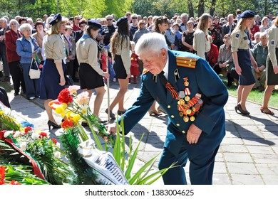 VISAGINAS, LITHUANIA - MAY 09, 2011: A veteran of the Great Second World War in the rank of colonel in uniform with orders and medals puts flowers on a monument at the Victory Day celebration