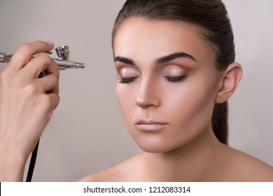 Visagist making makeup for model with aerograph, isolated on grey. Background with hand holding aerograph. Visagist using aerograph. Professional makeup for young woman in a beauty center. Beauty