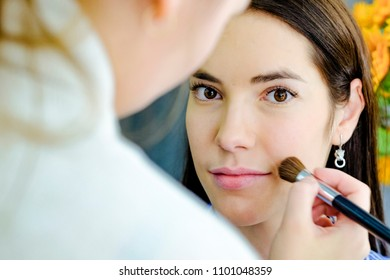 visagiste applying make up in beauty salon . reflection in the mirror. Yellow on the background. flowers  photo without retouch