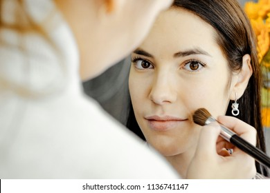 visagiste applying make up in beauty salon . reflection in the mirror. Yellow . flowers  on the background.  photo without retouch