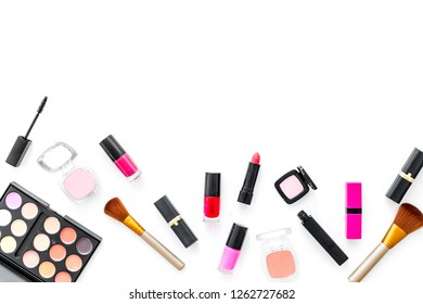 visagiste desk with decorative cosmetics: eyeshadows, lipstick, brush white background top view space for text