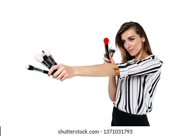 visagiste girl on a white background holding different and different size brushes in hands one of them is red, looks away