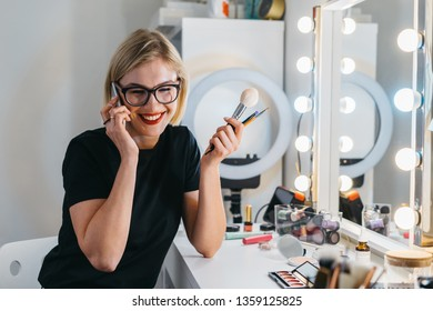 visagiste smiling talks by phone with client. stylish modern good looking blond female make up artist at work space. beauty professional uses gadget. female happy to answer mobile call