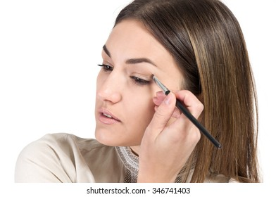 visagiste. young girl paints her eyes. Girl doing makeup. isolate