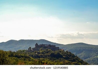Visegrad castle atop a hill with a beautiful sky lights behind