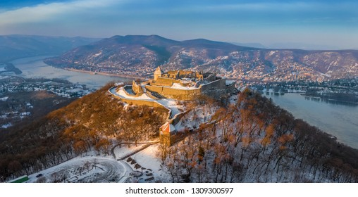 Visegrad, Hungary - Aerial panoramic view of the beautiful snowy high castle of Visegrad at sunrise on a winter morning with Dunakanyar at background