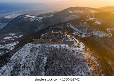 Visegrad, Hungary - Aerial panoramic view of the beautiful old and snowy high castle of Visegrad at sunrise on a winter morning with the hills of Pilis at background