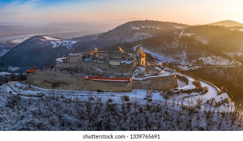 Visegrad, Hungary - Aerial panoramic view of the beautiful old and snowy high castle of Visegrad at sunrise on a winter morning