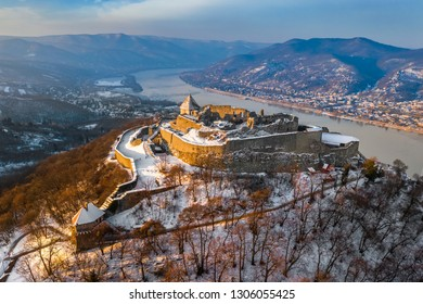 Visegrad, Hungary - Aerial view of the beautiful snowy high castle of Visegrad at sunrise on a winter morning with Dunakanyar at background