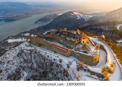 Visegrad, Hungary - Aerial view of the beautiful snowy high castle of Visegrad at sunrise with Dunakanyar at background. Winter morning