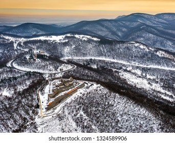 Visegrad, Hungary - Aerial view of the beautiful snowy hills of Pilis with old high castle of Visegrad at sunrise on a winter morning