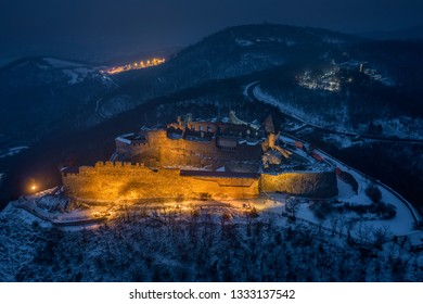 Visegrad, Hungary - Aerial view of the beautiful, illuminated high castle of Visegrad at blue hour with snowy hills of Pilis on a winter night