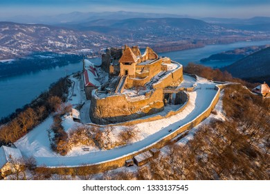 Visegrad, Hungary - Aerial view of the beautiful snowy high castle of Visegrad at sunrise with Dunakanyar at background on a winter morning