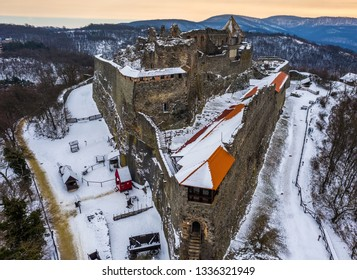 Visegrad, Hungary - Aerial view of the beautiful snowy high castle of Visegrad at sunrise on a winter morning with the hills of Pilis at background