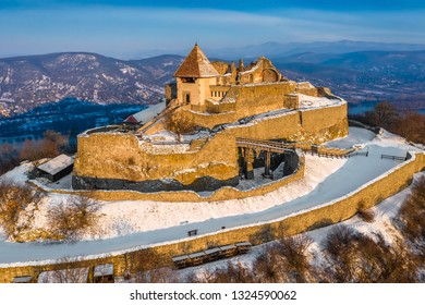 Visegrad, Hungary - The beautiful snowy high castle of Visegrad at sunrise with Dunakanyar at background on a winter morning on an aerial shot