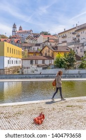 Viseu / Portugal - 04 16 2019 : View at the Viseu city, Church of Mercy on top, baroque style monument, architectural icon of the city of Viseu, people and a water mirror Portugal