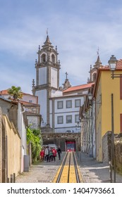 Viseu / Portugal - 04 16 2019 : View at the Viseu city, Church of Mercy on top, baroque style monument, architectural icon of the city of Viseu, diverse people, funicular and rails, in Portugal