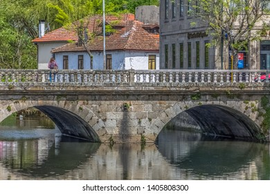 Viseu / Portugal - 04 16 2019 : View of the downtown area of Viseu with Pavia river and banks with buildings, trees and vegetation in Portugal