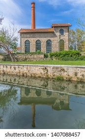 Viseu / Portugal - 04 16 2019 : View of the Museum of electricity, building with chimney in industrial brick, mirrored on Paiva river, Portugal
