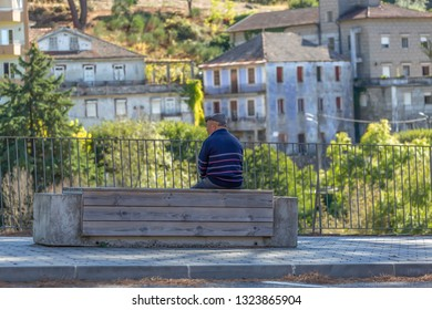 Viseu / Portugal - 10 05 2018: Back view of senior man relaxing sitting on a concrete and wooden bench on the pedestrian edge of a sidewalk road