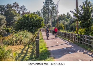 Viseu / Portugal - 10 05 2018: View of eco pedestrian / cycle lane, with two cyclists pedaling, two farmers and agricultural fields as background...