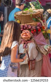 Viseu / Portugal - 10/06/2018 : View of farmer dolls, manipulated with people inside, carrying large traditional basket, at the Medieval market of Canas