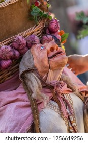 Viseu / Portugal - 10/06/2018 : View of farmer doll, manipulated with people inside, carrying large traditional basket, at the Medieval market of Canas
