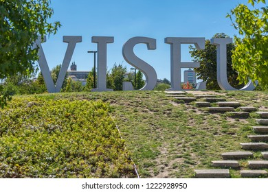Viseu / Portugal - 10/09/2018 : Large metallic letters with the name of city of Viseu, located in urban park of Viseu, background with historical center, in Portugal