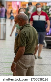 Viseu , Portugal - June 08 , 2020 : Old man watching store windows properly protected with face mask due to the pandemic of covid 19, corona virus
