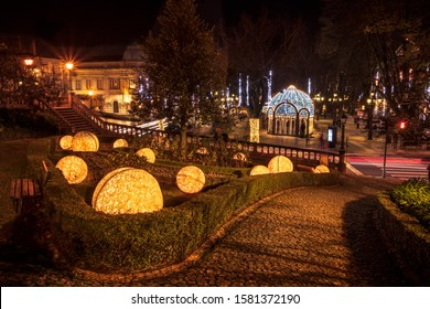 Viseu, Portugal - November 30, 2019: View of the Mother's Garden and Rossio Square with Christmas lights. In the garden we have balls with lights and in the the square a luminous bandstand.