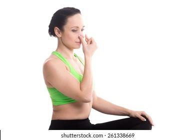 Vishnu Mudra for hatha yoga nadi Shodhan pranayama technique, serene girl practicing yoga, meditating, breathing through one nostril, copy space