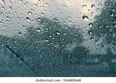 Visibility is limited when driving through a rain storm, raindrops splatter on the windshield. View through car window blurry with heavy rain.
