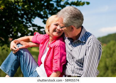 Visibly happy mature or senior couple outdoors arm in arm deeply in love, she is showing him something