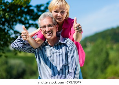 Visibly happy mature or senior couple outdoors arm in arm, he is carrying her piggyback