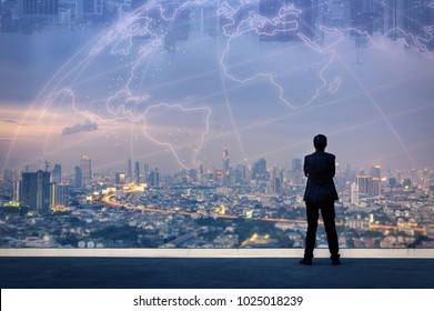 Vision concept. Successful businessman standing with hands crossed on chest, On top of building and looking through Cityscape Skyline Night Light.