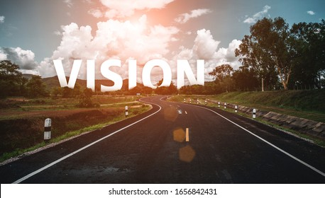 Vision concept. The word vision behind the tree of empty asphalt road at golden sunset and beautiful blue sky.