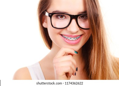 Vision and dentistry problems concept. Happy nerdy teenage in eyeglasses showing her braces on teeth