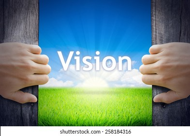 Vision. Hand opening an old wooden door and found Vision word floating over green field and bright blue Sky Sunrise.