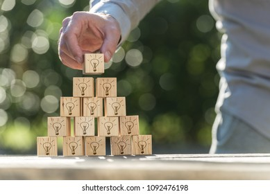 Vision and ideas concept of a man building a pyramid of wooden blocks with light bulb icons on them against sparkling bokeh.