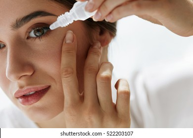Vision And Ophthalmology Medicine. Closeup Of Beautiful Woman Applying Eyedrops In Her Eyes. Young Female Model With Natural Makeup Using A Bottle Of Eye Drops. Health Concept. High Resolution