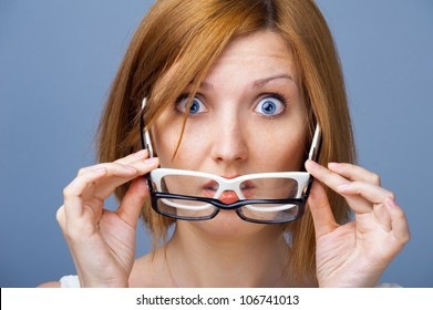 Vision without glasses. Amazed young woman with blue eyes holding two pairs of glasses in their hands