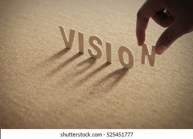 VISION wood word on compressed board with human's finger at N letter