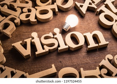 Vision word in scattered wood letters with glowing white light bulb