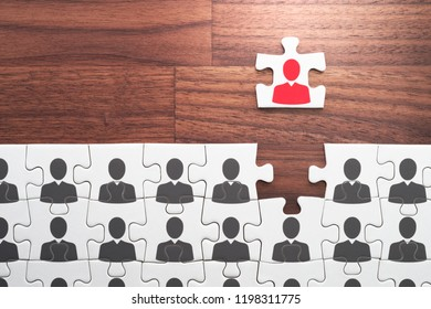Visionary leader, think positive, different and unique concept. Establishing leadership position.Jigsaw puzzle piece with red businessperson standing out from the crowd.