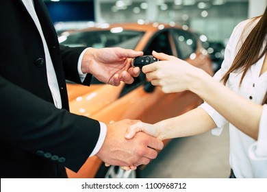 The visit to the dealership ended with the purchase of a car. The seller hands over the keys to the buyer on the back of a car dealership