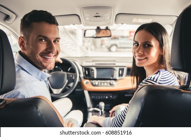Visiting car dealership. Beautiful couple is looking at camera and smiling while sitting in their new car