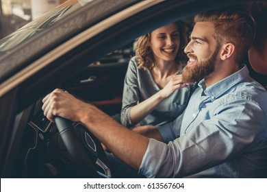 Visiting car dealership. Beautiful couple is talking and smiling while sitting in their new car