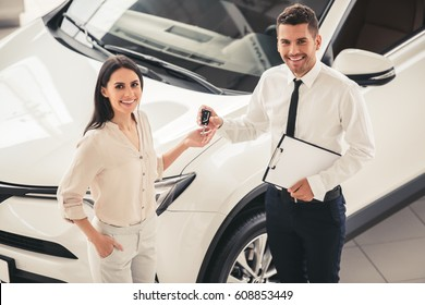 Visiting car dealership. Beautiful young woman and handsome sales manager are holding key, looking at camera and smiling